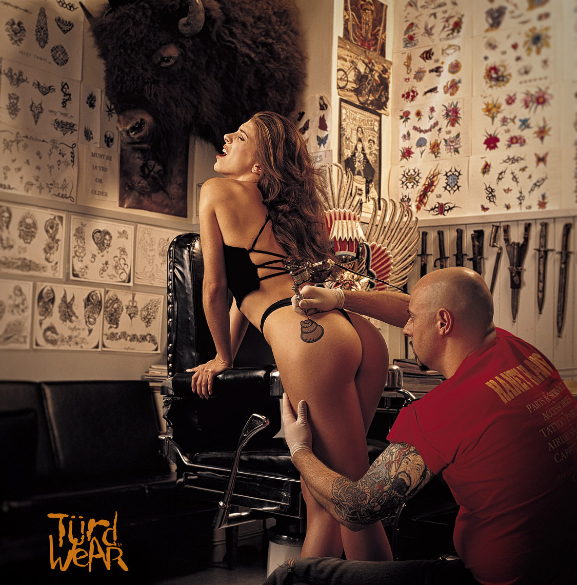 attractive girl gets a tattoo on her bum in a tattoo shop